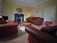 Comfortable guest lounge with settees and wood burning stove
